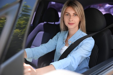 Woman with fastened safety belt on driver's seat in car