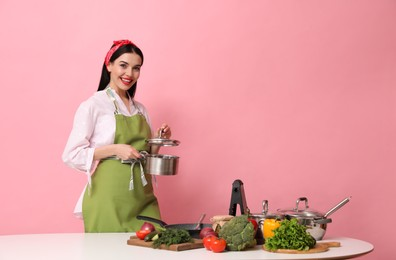 Young housewife with vegetables and different utensils on pink background. Space for text