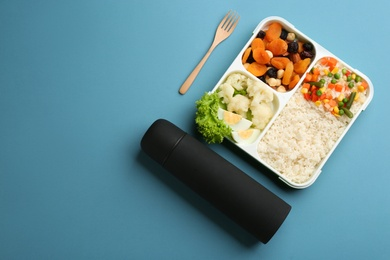 Thermos and lunch box with food on light blue background, flat lay. Space for text