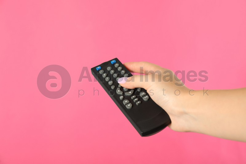 Woman holding remote control on pink background, closeup