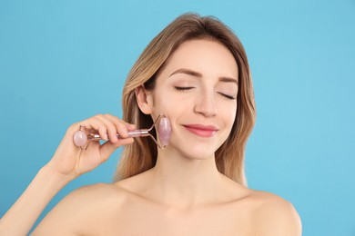 Young woman using natural rose quartz face roller on light blue background