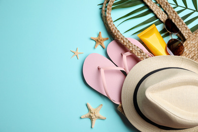 Flat lay composition with beach objects on light blue background. Space for text