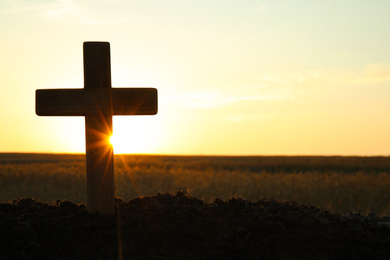 Silhouette of Christian cross outdoors at sunrise, space for text. Religion concept