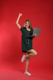 Full length portrait of emotional woman with modern laptop on red background