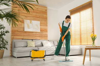 Woman cleaning floor with mop at home