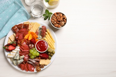 Plate of different appetizers with dip sauce on white wooden table, flat lay. Space for text