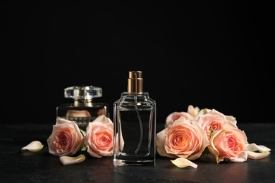 Bottle of perfume and beautiful roses on black table
