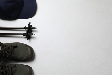Flat lay composition with trekking poles and other hiking equipment on light background, space for text
