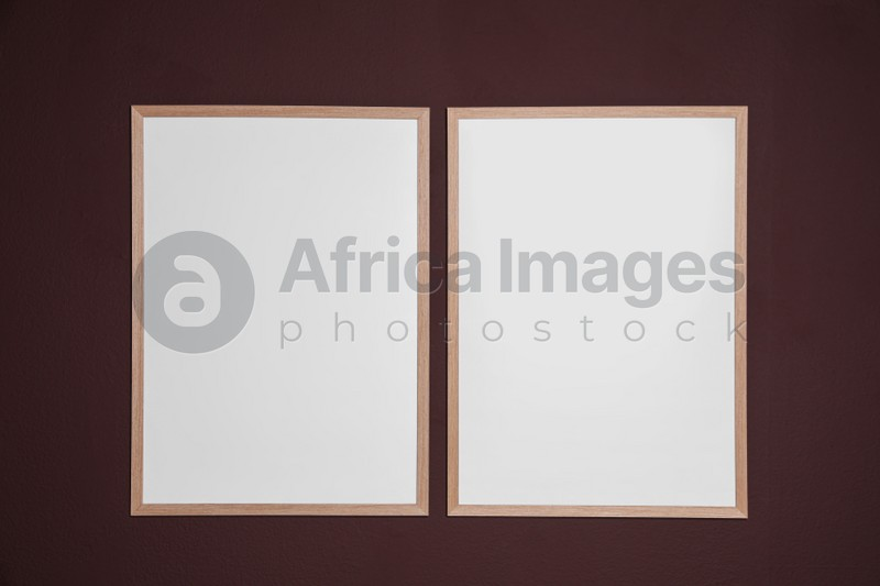 Empty frames on brown wall. Mockup for design