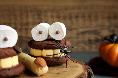 Delicious desserts decorated as monsters on stump, closeup. Halloween treat