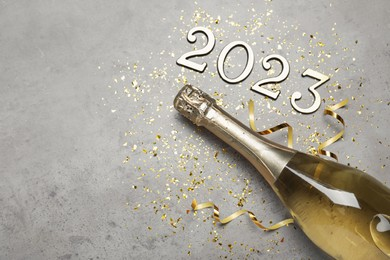 Bottle of sparkling wine, festive decor and number 2023 on grey background, flat lay with space for text. Happy New Year