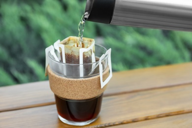 Pouring hot water into glass with drip coffee bag from thermos on wooden table, closeup
