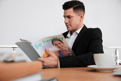 Man reading magazine at table in office