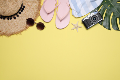 Flat lay composition with beach objects on yellow background. Space for text