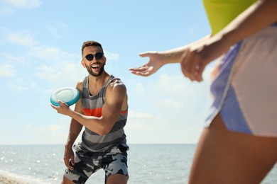 Couple playing with flying disk at beach on sunny day