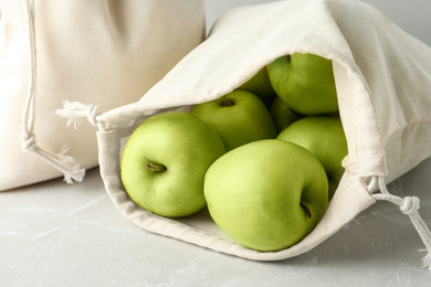 Cotton eco bags with apples on marble table, closeup