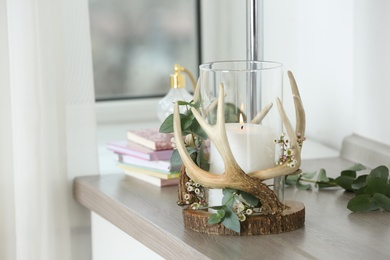 Burning candle in beautiful glass holder on wooden table indoors