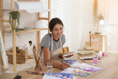 Young woman drawing flowers with watercolors at table indoors