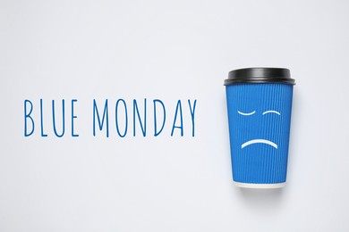 Takeaway cup and text Blue Monday on white background, top view