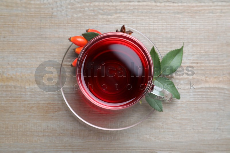 Aromatic rose hip tea and fresh berries wooden table, top view