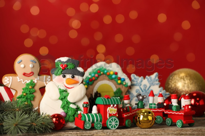 Sweet Christmas cookies and decor on wooden table against blurred festive lights. Space for text