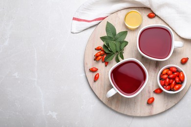 Fresh rose hip tea and berries on light table, flat lay. Space for text