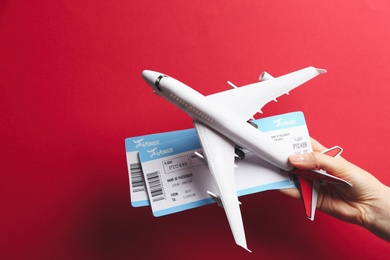 Woman holding toy airplane and tickets on red background, closeup