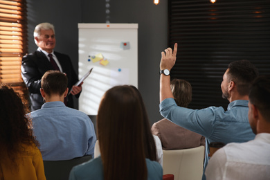 Man raising hand to ask question at seminar in office