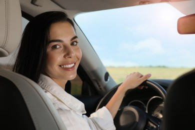 Beautiful young woman on driver's seat in modern car