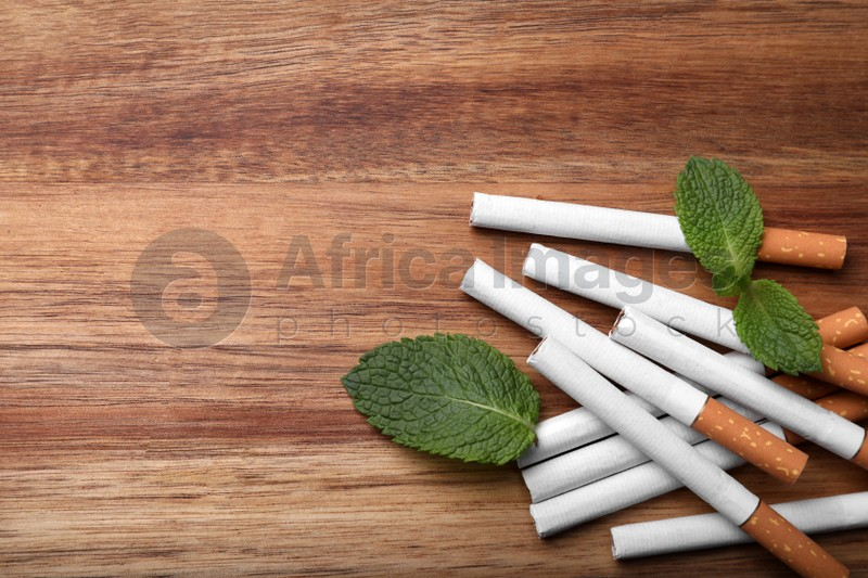 Menthol cigarettes and mint leaves on wooden table, flat lay. Space for text