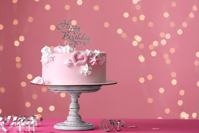 Beautifully decorated birthday cake on pink table against blurred festive lights, space for text