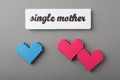 Hearts and text Single mother on grey background, flat lay