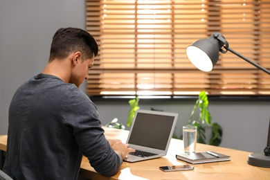 Man using laptop for search at wooden table in office