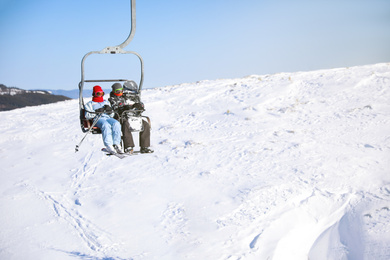 People using chairlift at mountain ski resort, space for text. Winter vacation