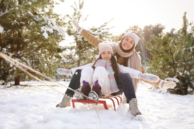 Happy mother and daughter sledding outdoors on winter day. Christmas vacation