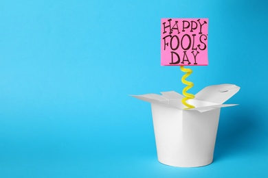 Lunch box with Happy Fools' Day note on light blue background. Space for text