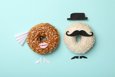 Bride and groom made with donuts on light blue background, flat lay