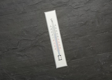 Weather thermometer on black slate background, top view