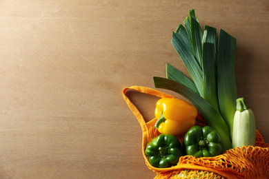 Different fresh vegetables in eco mesh bag on wooden table, top view
