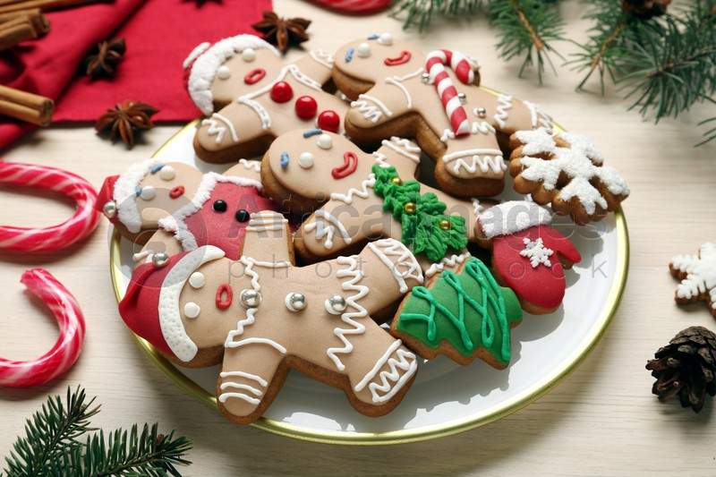 Delicious Christmas cookies, candies and fir branches on beige table
