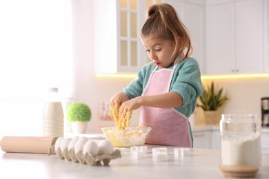 Little girl making dough at table in kitchen