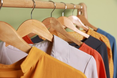 Collection of trendy women's garments on rack near green wall, closeup. Clothing rental service