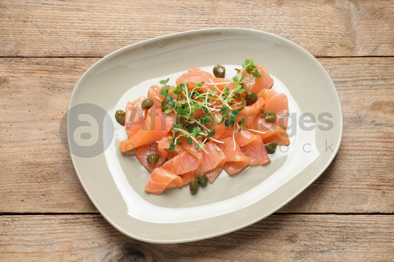 Delicious salmon carpaccio served on wooden table, top view