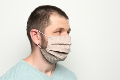 Man wearing handmade cloth mask on white background, space for text. Personal protective equipment during COVID-19 pandemic