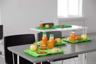 Trays with healthy food on table in school canteen