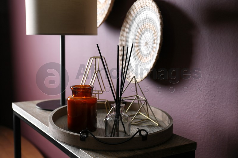 Wooden tray with decorations and lamp on table indoors