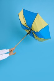 Woman with umbrella caught in gust of wind on light blue background, closeup