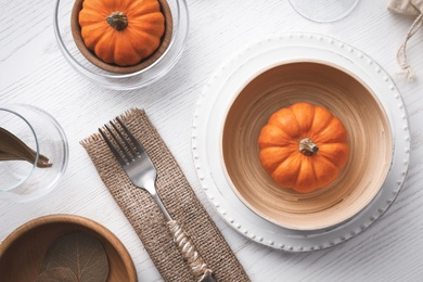 Autumn table setting with pumpkins on white wooden background, flat lay