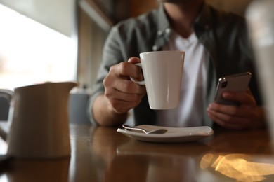Man with cup of coffee and smartphone at table in morning, closeup