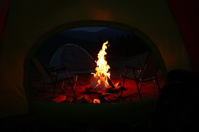 Beautiful bonfire and folding chairs outdoors in evening, view from camping tent